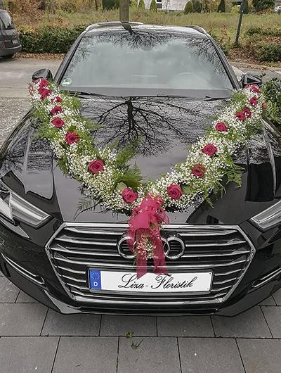 Hochzeit - Autoschmuck mit einer Girlande auf einem Audi